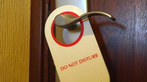 Do Not Disturb sign swinging on hotel room door. Red white door hanger on handle close-up.
