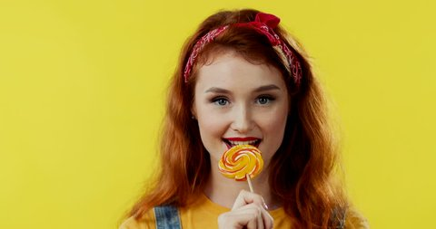 Close up of the young attractive Caucasian girl withh red hair licking lollipop and smiling to the camera on the yellow background. Portrait.