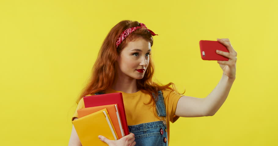 Young beautiful Caucasian red-haired woman with textbooks in hands smiling to the smartphone camera while taking selfie photos on the yellow background.