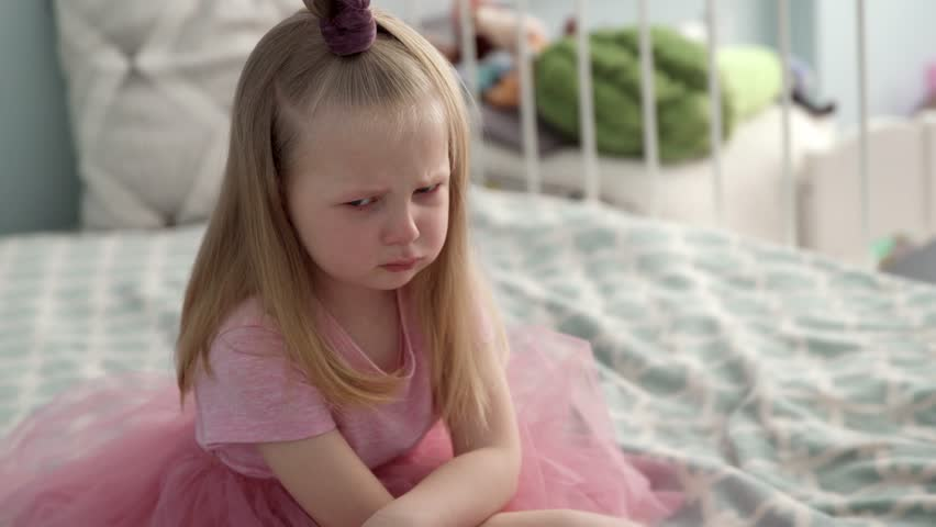 The little girl in the pink dress is very angry and upset, frowning her brow and showing tongue. Bad mannered little girl with blond hair. Crying on the bed | Shutterstock HD Video #1027079411