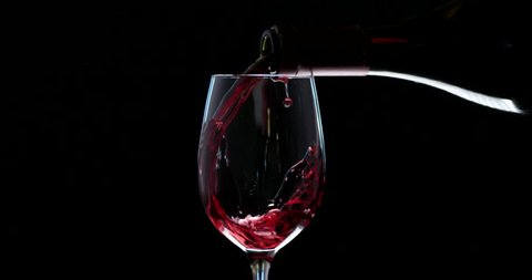Hand pouring wine into the glass. Slow motion of spilling alcohol over black background. RED camera