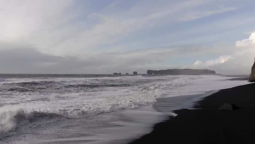 Breaking wave and Reynisdrangar rock formations offshore black volcanic Reynisfjara sand beach. Peace and tranquility