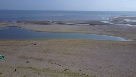 Flying with drone straight forward over flat beach in the netherlands in sunny weather and blue sky. Little lagoon in flat and calm water. Quiet and relaxed atmosphere.