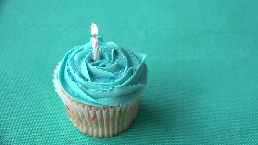 One Cupcake Frosted With Blue Icing And A White Birthday Candle That Is Lit It Isolated On Background