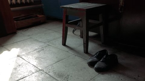 Old grunge shoes in dark empty room by chair