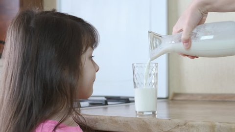 The child is poured milk. Little girl drinks milk in the kitchen.