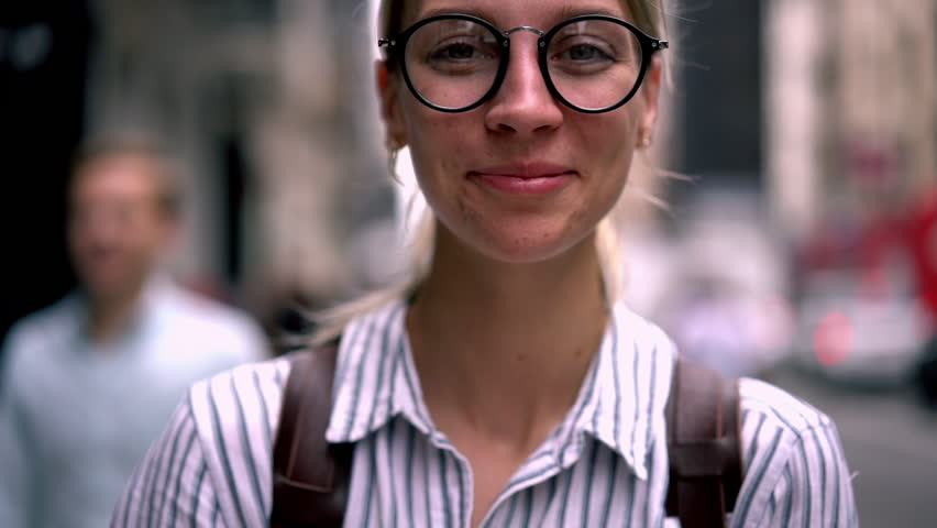 Closeup portrait of sincerely happy caucasian hipster girl with beautiful eyes in eyewear smiling for camera. laughing female using mobile phone application while standing outdoors on city street | Shutterstock HD Video #1027330781