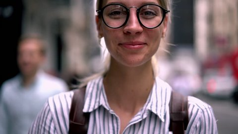 Closeup portrait of sincerely happy caucasian hipster girl with beautiful eyes in eyewear smiling for camera. laughing female using mobile phone application while standing outdoors on city street