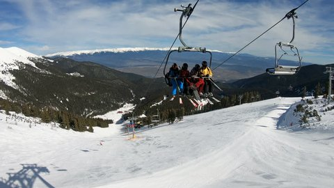 Bansko, Bulgaria - circa Feb, 2018: Ski lift transporting skiers, snowboarders at top of world cup ski piste Tomba in Bansko, Bulgaria with view of Banderitsa at background