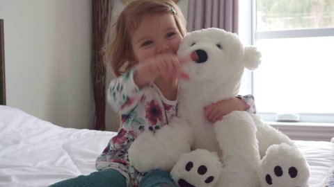 A Cute little girl in pajama hugging her toy hare on the bed at home