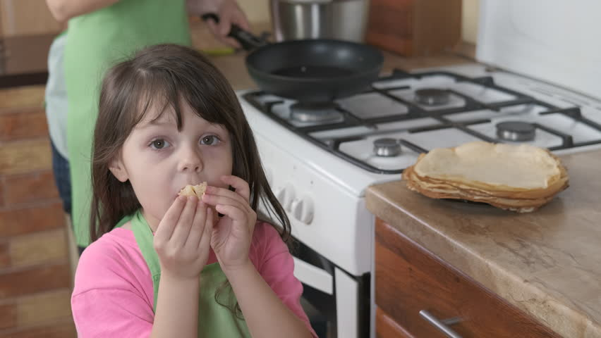Woman with a kid cook in the kitchen. A child in the kitchen eats pancakes. | Shutterstock HD Video #1027406681