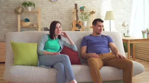 Young man farted sitting on the couch next to a young woman who wore a respirator from the smell