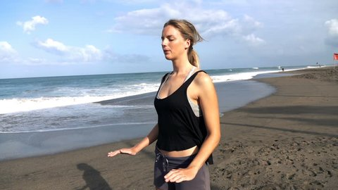 Young pretty woman meditating on the beach, super slow motion