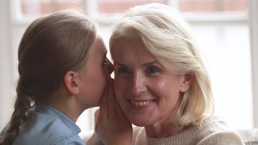 Loving old grandmother listening to cute little granddaughter whispering in ear telling secret, happy understanding senior grandma and grandchild girl gossiping secretly talking, trust concept | Shutterstock HD Video #1027488491