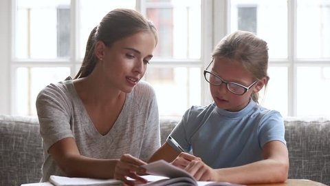 Caring mom babysitter teacher helping kid daughter with homework, parent mother teaching child read book and cute school girl learning writing in textbook studying at home, family education together