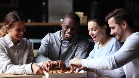 Multicultural happy friends talking laughing sharing takeaway pizza meal together in cafe indoors, smiling diverse young mates students having fun eating food together at meeting sitting at table