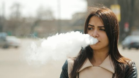 positive woman smoking e-cigarette on the road with cars driving by on the background