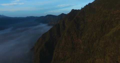 Drone shot of the Bromo mountains, with a sea of clouds at the bottom during sunrise