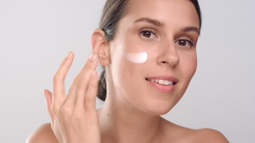 Close-up beauty portrait of young positive brown-haired Caucasian woman with perfect smooth healthy skin applies cream on her face, looks at the camera and smiles   Skin care commercial concept   Shutterstock HD Video #1027606841
