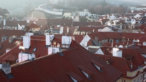 Prague, Czech Republic - February 2019: Elevated city view with red tiled roofs of Lesser Town of Prague and smoke coming out of chimneys. 4K resolution