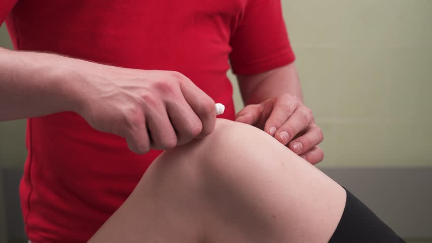 Close-up demonstration video of a professional therapists applying cream onto a patients knee with massage movements. Sport massage concept. Knee joint pain relief therapy | Shutterstock HD Video #1027633421