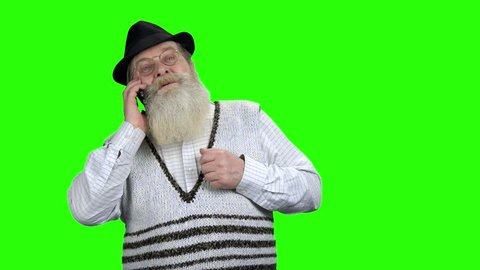 Serious old man talking on cell phone. Aged business man with long beard using mobile phone on Chroma Key background.