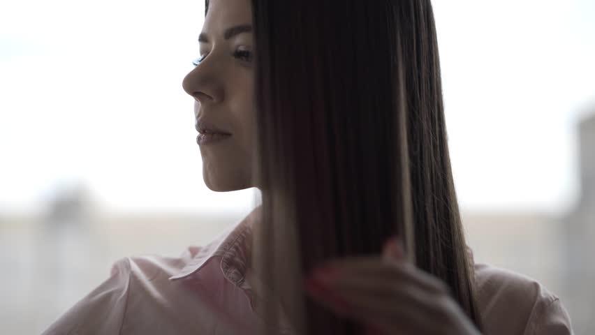 Brunette girl in a pink shirt is combing her beautiful long hair comb   Shutterstock HD Video #1027672601