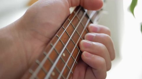 Closeup of Beautiful, Vintage Wooden Ukulele musical instrument,. A Musician is holding the instrument, about to play the strings.