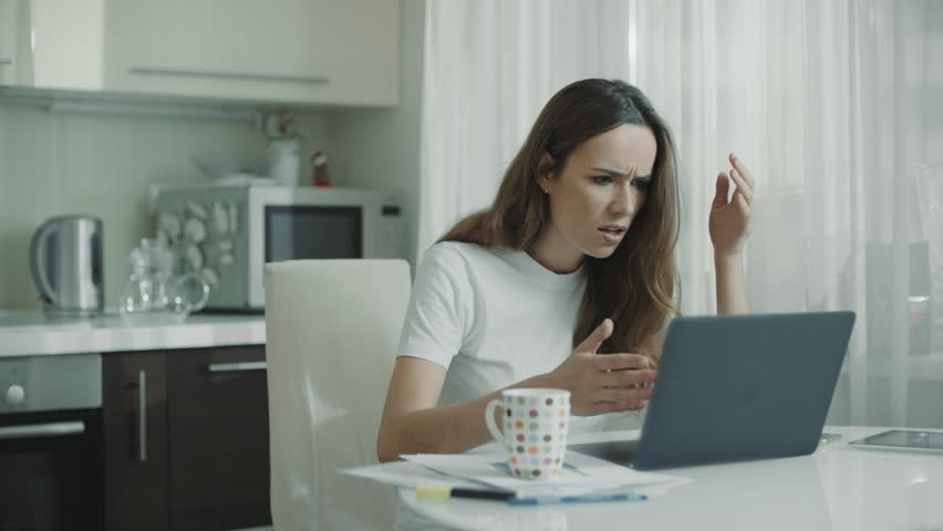 Angry woman typing on laptop computer at kitchen. Worried woman working online laptop at home workplace. Stressed girl looking at laptop screen at home. Female freelancer stress   Shutterstock HD Video #1027710641