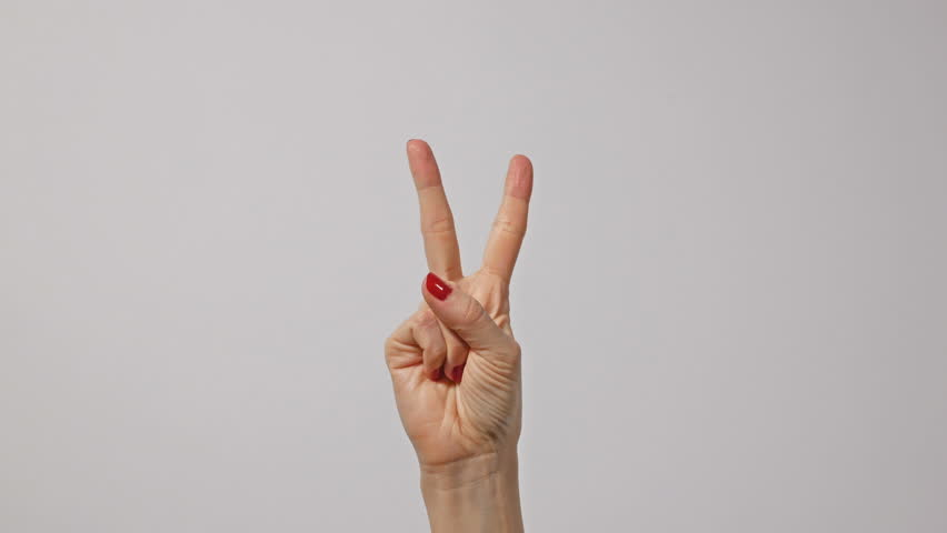 Woman raising two fingers up and showing peace or victory symbol or letter V. Female one hand holding two fingers up in sign language on light background. Fingernails with fresh red glossy manicure