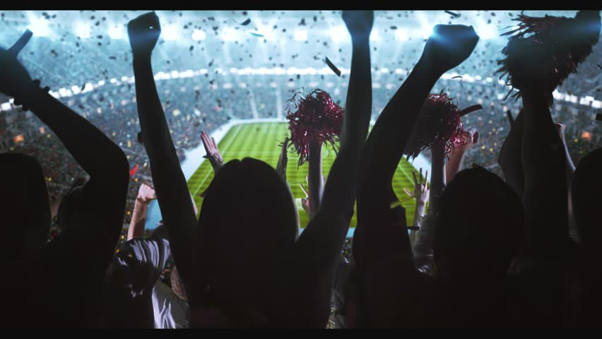 Group of cheering fans watch a sport championship on stadium. Their team wins and everybody are celebrating this event. People are dressed in casual clothes. Colorful confetti fly in the air. | Shutterstock HD Video #1027762931