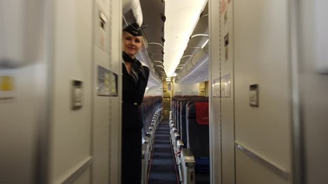 MOSCOW - APRIL, 2019: POV Walking inside Aeroflot Russian Airlplane with welcome hostess. Aeroflot is the flag carrier and largest airline of the Russian Federation.