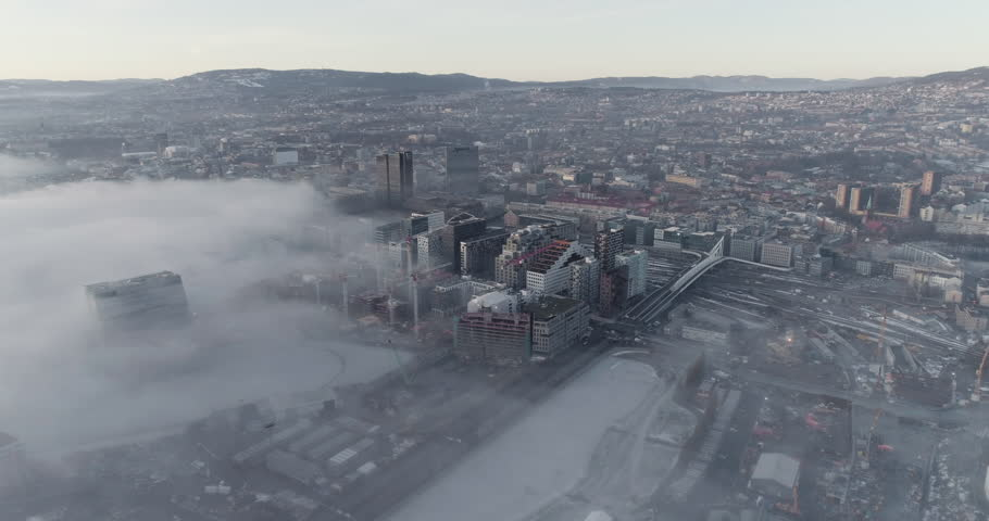 4K aerial video with pan motion and a high angle view of the beautiful Oslo skyline, the unique and modern buildings in the Opera quarter covered in fog and the Holmenkollen hills after sunset.   Shutterstock HD Video #1027773131