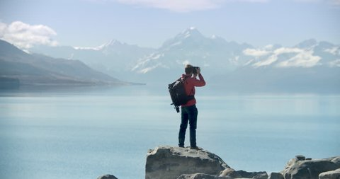 Travel blogger taking photographs in New Zealand. Lake with Mt Cook in background. Video clip recorded on professional camera, 10bit Pro Res in slo-motion.
