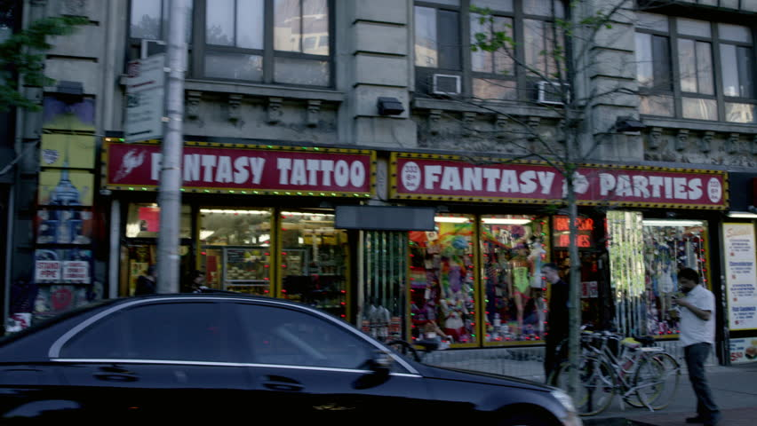 NEW YORK - MAY 23, 2015: Papaya Dog, fantasy sex and tattoo shops on Waverly Place, West Village, West 4th Street on 6th Ave, 4K NY. Greenwich Village is a neighborhood in Manhattan, NYC, USA.