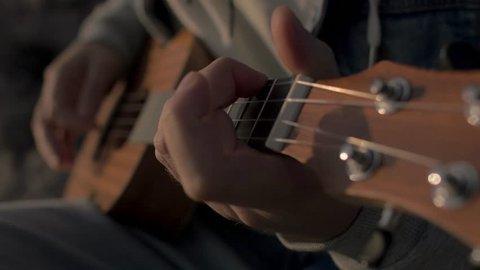 4K Playing on the ukulele at sunset close-up