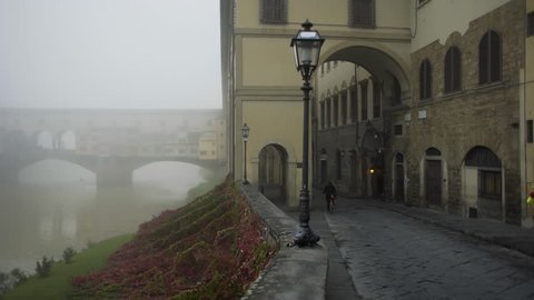 Pan of Ponte Vecchio on foggy morning in Florence Italy