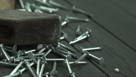 Hammer and nails on black wooden background close up