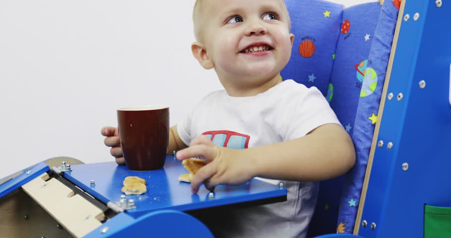 Functional toy car with a table. The child sits and eats cookies and drinks tea. Happy little boy have fun.  Educational toy Montessori. Fine motor skills. Sensory sensitivity.   Shutterstock HD Video #1027889981