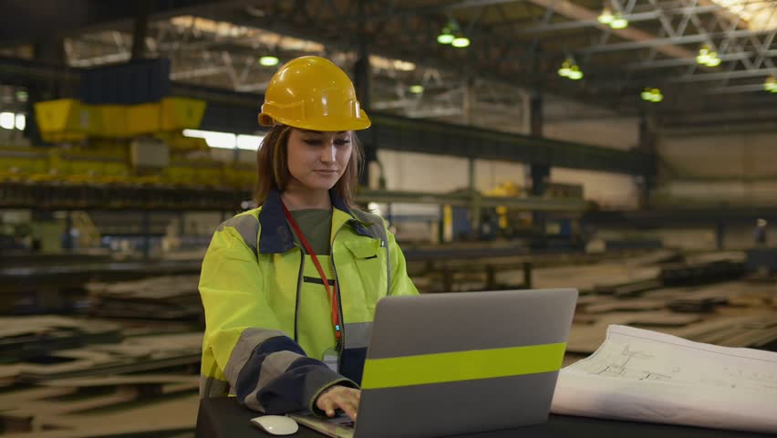 Young beautiful female in protective uniform and helmet using laptop while working at plant | Shutterstock HD Video #1027919591