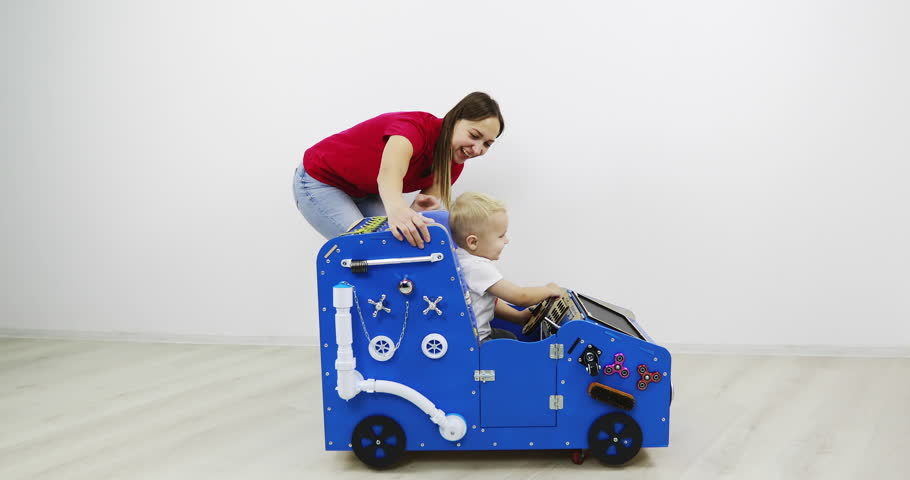 Mom and her little son are playing with a developing machine. Educational toy Montessori. Fine motor skills. Sensory sensitivity.   Shutterstock HD Video #1027920821