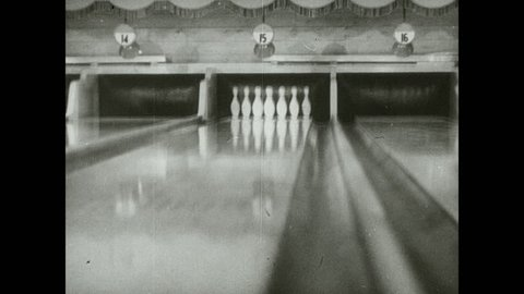 1930s: Bowling ball travels down lane, knocks down all pins. Woman stands at top of lanes.