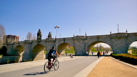 Madrid / Spain - 03 17 2019: A slow motion of people walking next to the Toledo old bridge and doing sport at Madrid Rio green park along the Manzanares river downtown Madrid on a warm spring day
