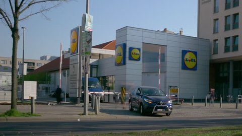BERLIN, GERMANY - APRIL 18, 2019: Time Lapse: People And Traffic At Lidl Discount Supermarket In Berlin, Germany In Spring