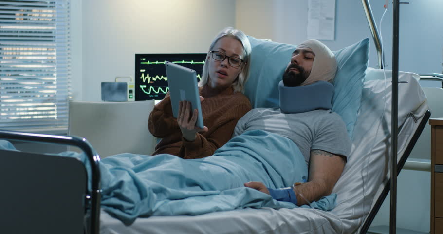 Medium shot of a woman using a tablet with her injured boyfriend in a hospital #1027955591