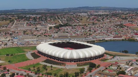 Port Elizabeth, South Africa - circa 2010s: Wide aerial flies toward Nelson Mandela Bay Stadium, overlooking the North End Lake. Forward flight, tilt down onto green pitch reveals lawnmower at work