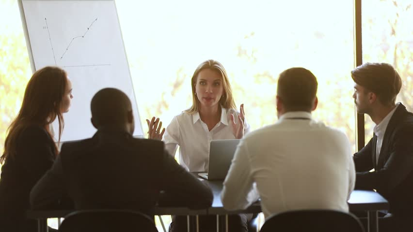 Female business coach mentor teacher talking at diverse staff group office meeting sit at table, executive manager boss leader training employees interns consulting clients at team corporate workshop