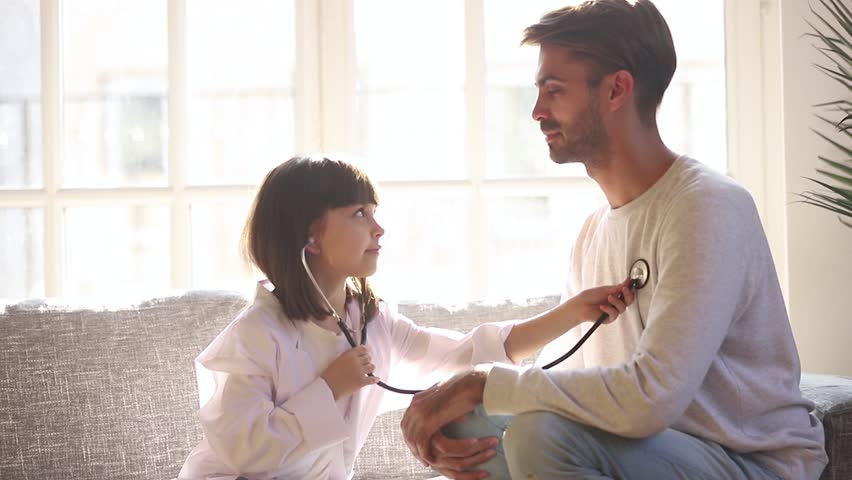 Cute small child daughter dressed in white coat holding stethoscope listening to father patient at home, funny little kid girl playing game as doctor pretending nurse having fun with dad sit on sofa