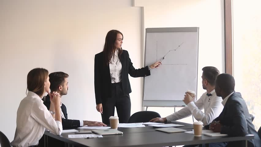 Young woman business leader manager coach give flip chart presentation explain graph for diverse employees group at office meeting training, female mentor teacher consult team at corporate workshop