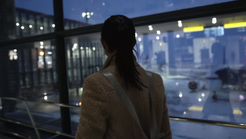 Backview of young traveller girl walking on airport. Travelling concept. Modern interiors with huge windows and reflections #1028041391